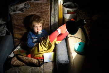 Child Sitting On a Chair In a Dark Room In Front Of The Lamp