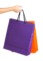 Two paper Shopping bags in woman hand with reflection on white