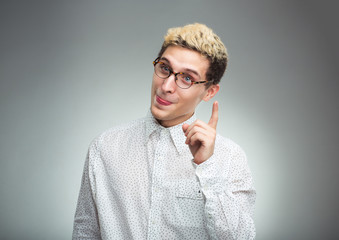 Young man in glasses with a funny expression on his face and thu