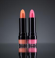 Two bright lipsticks on a black