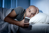 young internet addict man in bed using mobile smartphone poster