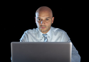 concentrated businessman working on computer laptop late night