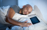 internet addict man at night in bed with digital pad or tablet poster
