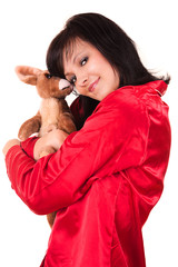 Young woman in red pyjamas with teddy bear, white background