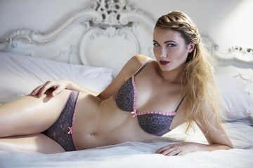Blonde woman lying on bed