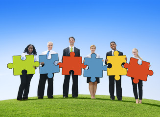Business People Holding Jigsaw Pieces Outdoors