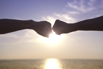 夕日と伸ばした2人の腕