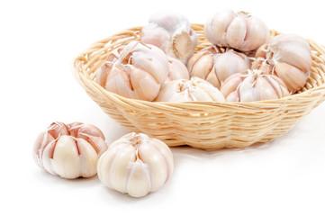 Fresh organic garlic in bamboo basket on white background