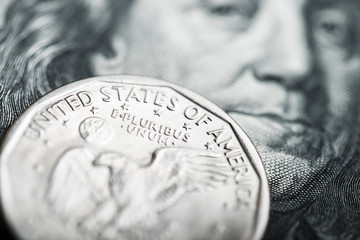 close-up of one dollar coin on the one hundred Dollar bill
