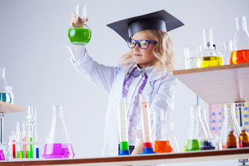 Young chemist posing with variety of reagents