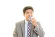 水を飲む笑顔のビジネスマン