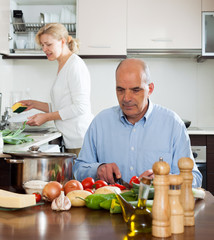 Elderly senior preparing vegetarian food and mature wife doing