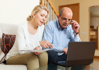 Serious man adn woman reading finance documents together