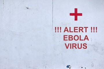 White Wall with Red Cross  and text ALERT EBOLA VIRUS