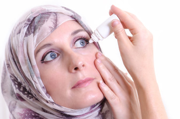 Arabic woman applying eye drops