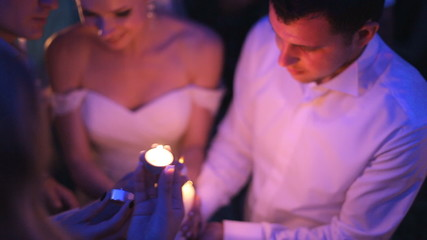 Guests at a wedding set fire to their candles from the large
