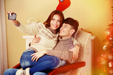 Young couple with mobile phone sitting in rocking chair near