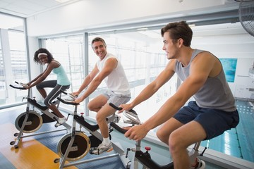 Three fit people working out on exercise bikes