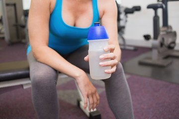 Fit brunette holding sports bottle