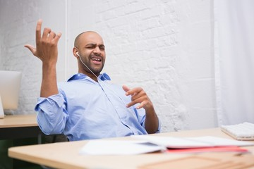 Businessman listening music while playing air guitar in office
