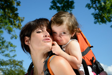 a little girl in a baby carrier walks with his mom