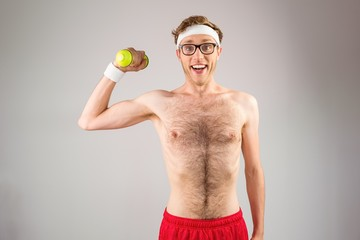Geeky shirtless hipster posing with dumbbell