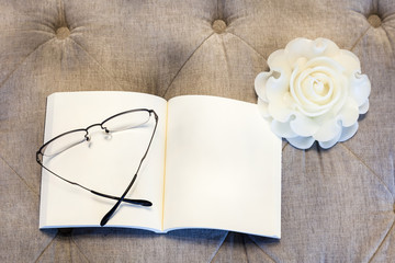 Blank  book with rose candle on sofa with eyeglasses