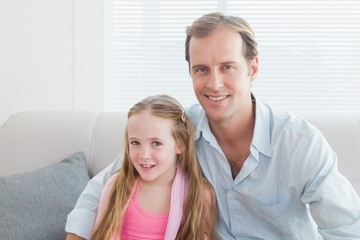Casual father and daughter smiling at camera