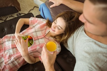 Cute couple relaxing on couch at breakfast