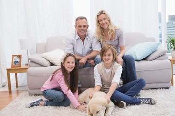 Smiling family with their pet yellow labrador on the rug