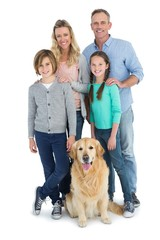 Portrait of smiling family standing together with their dog