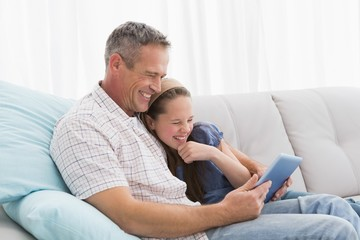 Father with daughter relaxing on the couch using laptop