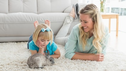 Smiling daughter and mother laying on the floor with rabbit