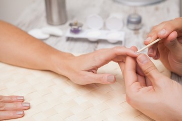 Manicurist cleaning a customers nails