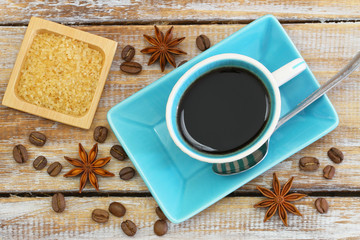 Cup of black coffee, brown sugar, coffee beans and star anise