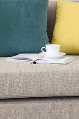 Coffee and book on Sofa with pillows