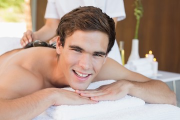 Handsome man receiving stone massage at spa center