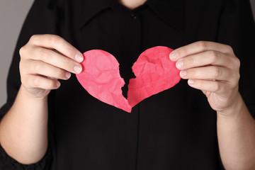Crumpled torn heart in women hands