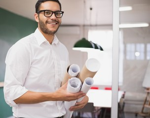 Casual architect smiling at camera holding blueprints