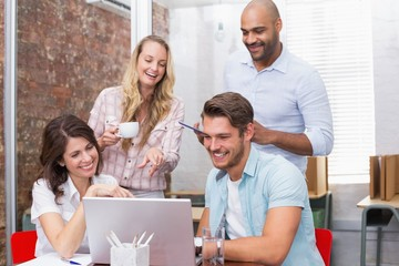 Business team laughing together in front of the laptop