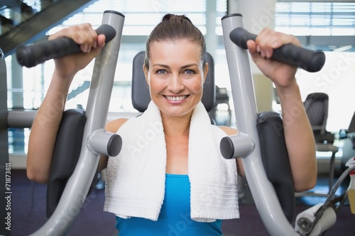 canvas print picture Fit brunette using weights machine for arms