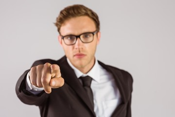 Young serious businessman pointing at camera