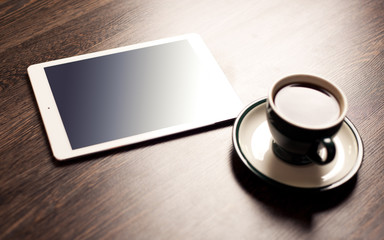 Digital tablet computer with cup of coffee on old wooden desk