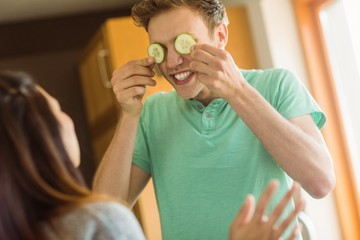 Cute man holding cucumber slices over eyes