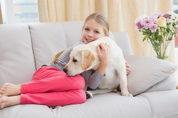 Cute little girl with her puppy on couch