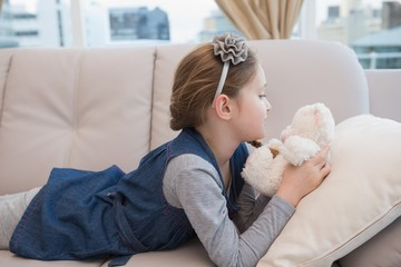 Little girl lying on the couch with teddy
