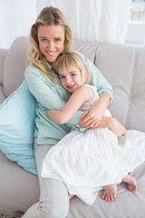 Mother sitting on the couch with her daughter smiling at camera