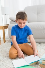 Little boy sitting on the floor reading storybook