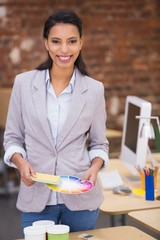 Businesswoman holding color wheel in office
