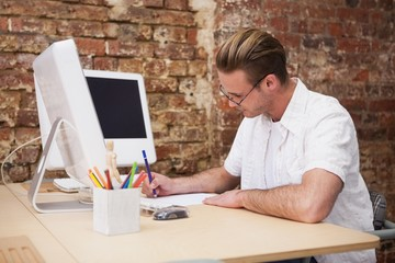Handsome happy man using computer taking notes